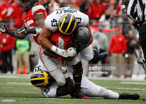 T Barrett of the Ohio State Buckeyes is tackled by Chris Wormley and Taco Charlton of the Michigan Wolverines during the first half of their game at...