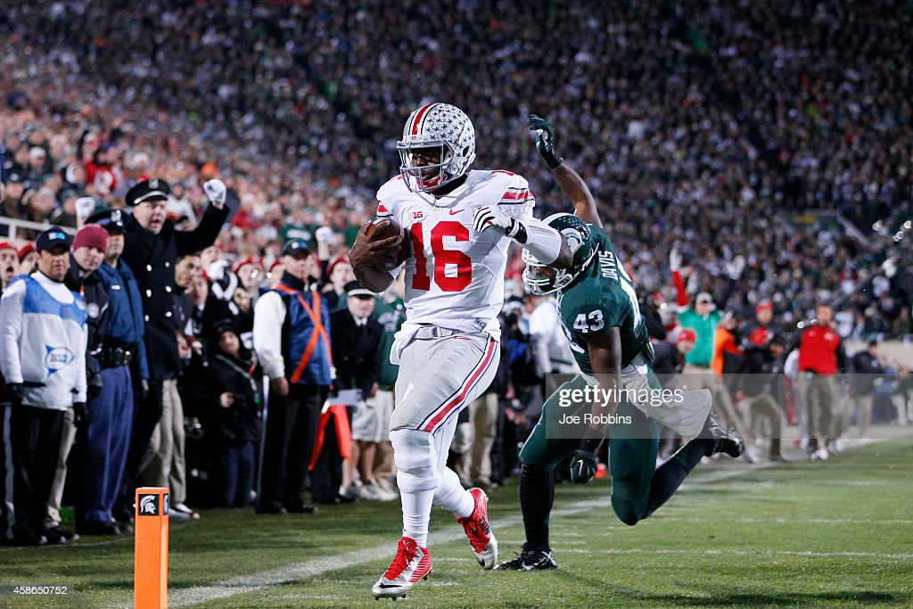 T Barrett of the Ohio State Buckeyes runs for a fiveyard touchdown in the first quarter of the game against the Michigan State Spartans at Spartan...