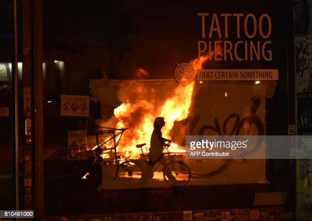 A barricade fire is reflected in a store window on July 7 2017 in Hamburg northern Germany where leaders of the world's top economies gather for a...
