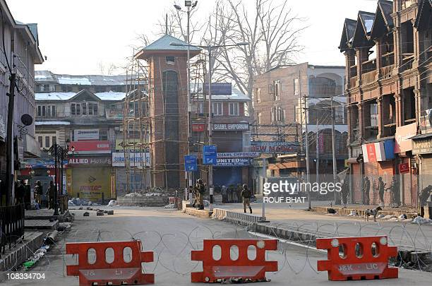 Barricades are seen as Indian paramilitary personnel stand guard during a curfew at the central Lal Chowk clock tower area of Srinagar on January 26...