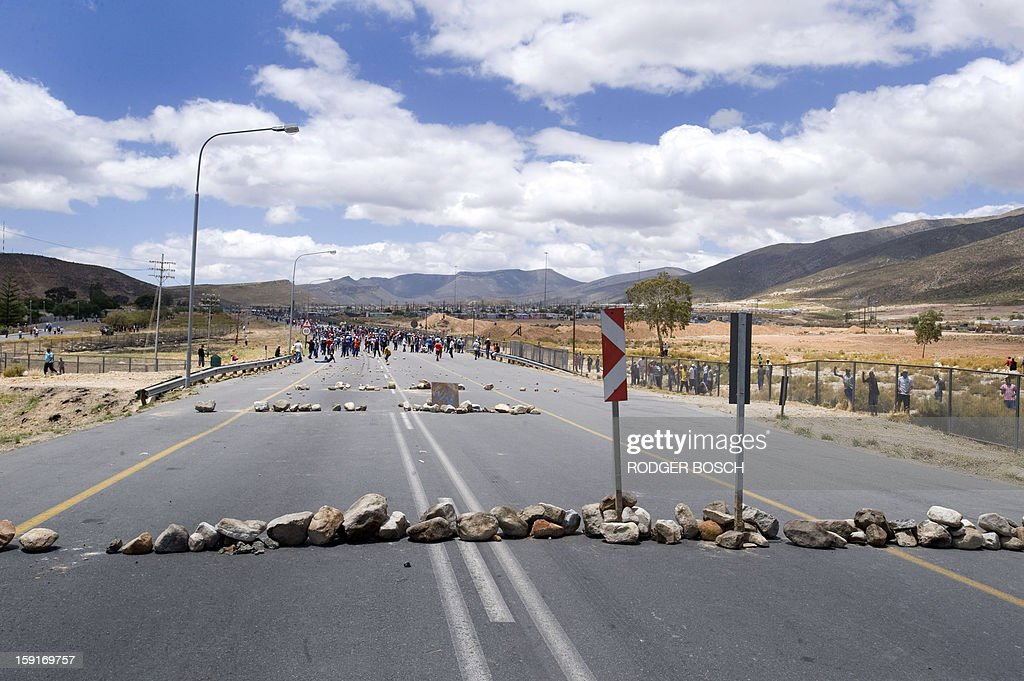 Barricades of rock lie across the N1 Highway set down by striking farm workers and other protestors after clashes broke out with anti-riot police forces on January 9, 2013 in De Doorns, a small farming town about 140km north of Cape Town, South Africa. Workers on fruit farms have downed tools, demanding a wage hike from 69 rand ($8) to 150 rand ($17.50) a day. The protesters also occupied part of the country's major N1 highway, forcing dozens of police officers and two armoured vehicles to move down the road, pushing the protesters back from the town entrance. AFP PHOTO / RODGER BOSCH