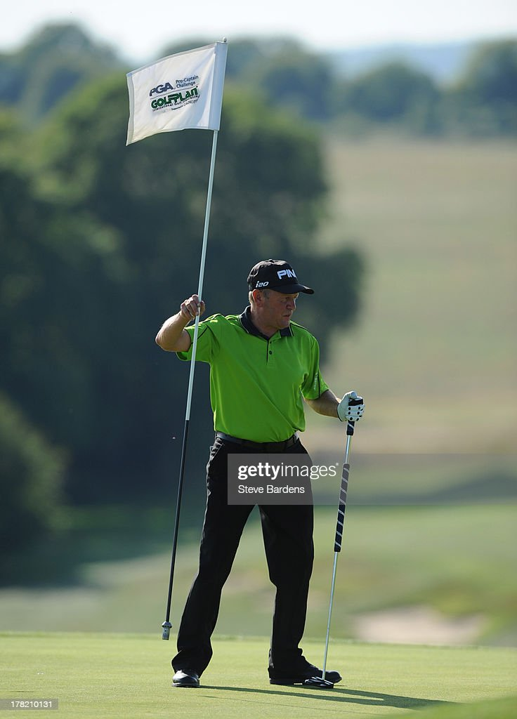 Barrie Stevens of Beau Desert golf club moves a flag during the Golfplan Challenge Regional Qualifier at Golf at Goodwood on August 27, 2013 in Chichester, England.