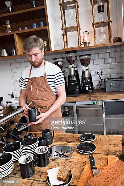 Barrista heats milk in cafe