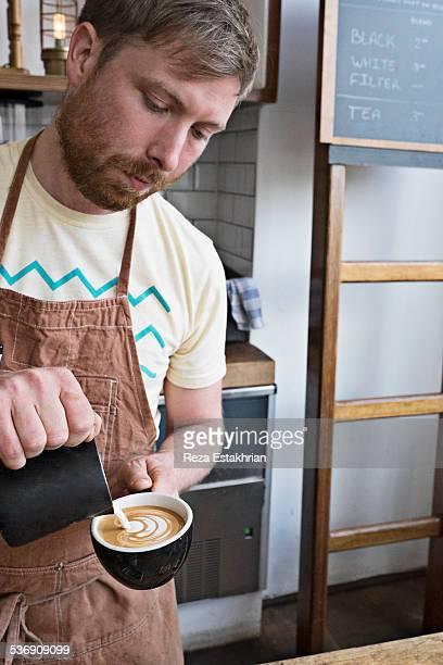 Barrista pours milk swirl on cappucino