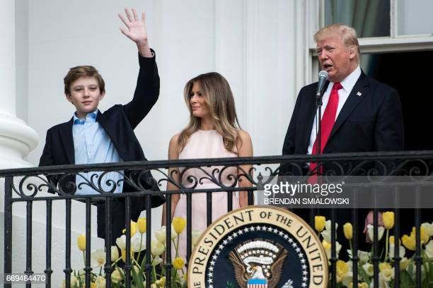 Barron Trump waves while standing with US First Lady Melania Trump and US President Donald Trump during the Easter Egg Roll on the South Lawn of the...