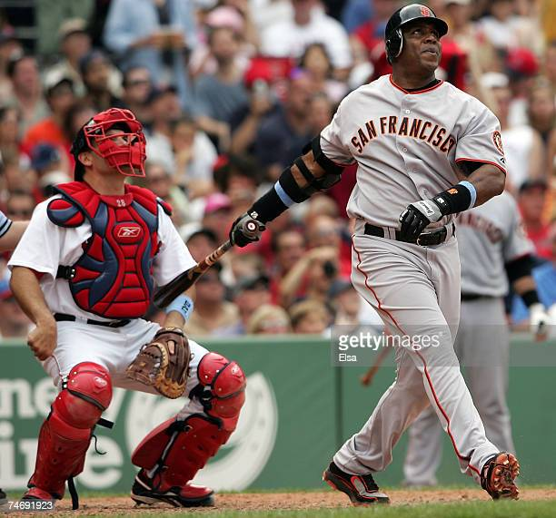 Barry Bonds of the San Francisco Giants hits a solo home run in the sixth inning as Doug Mirabelli of the Boston Red Sox looks on on June 17 2007 at...