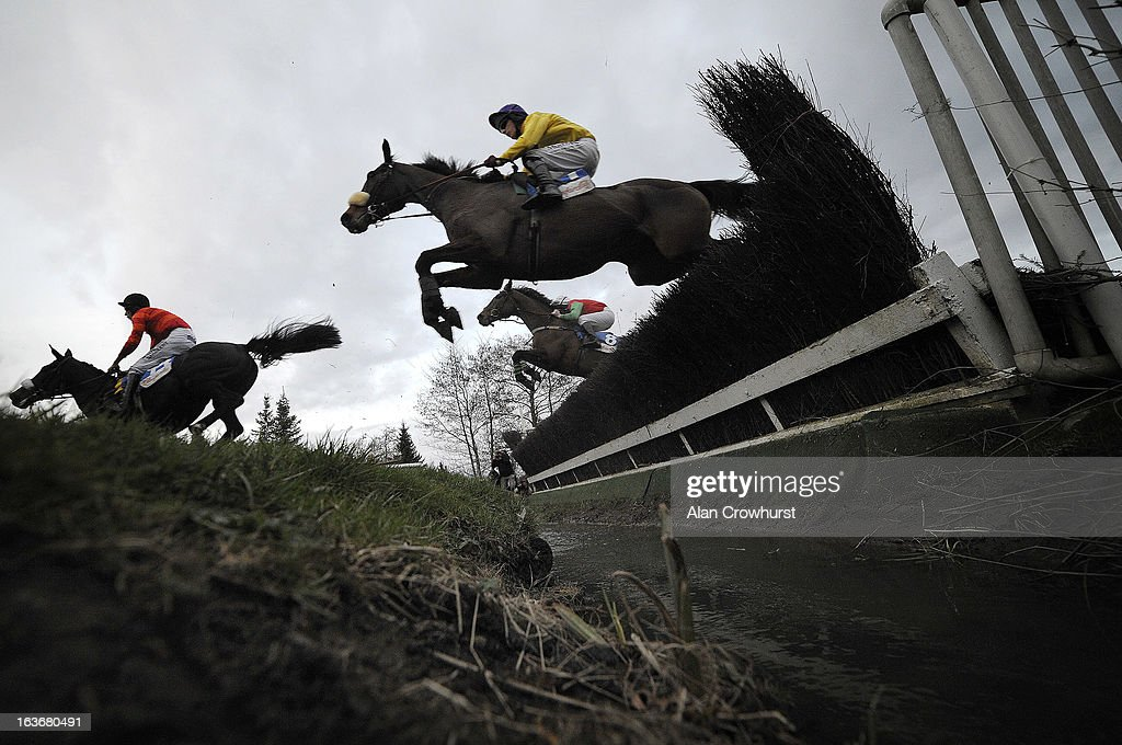 Barry Cash riding Big Shu (C, bottom) clear the water jump before winning The Glenfarclas Handicap Steeple Chase during St Patrick's Thursday at Cheltenham racecourse on March 14, 2013 in Cheltenham, England.