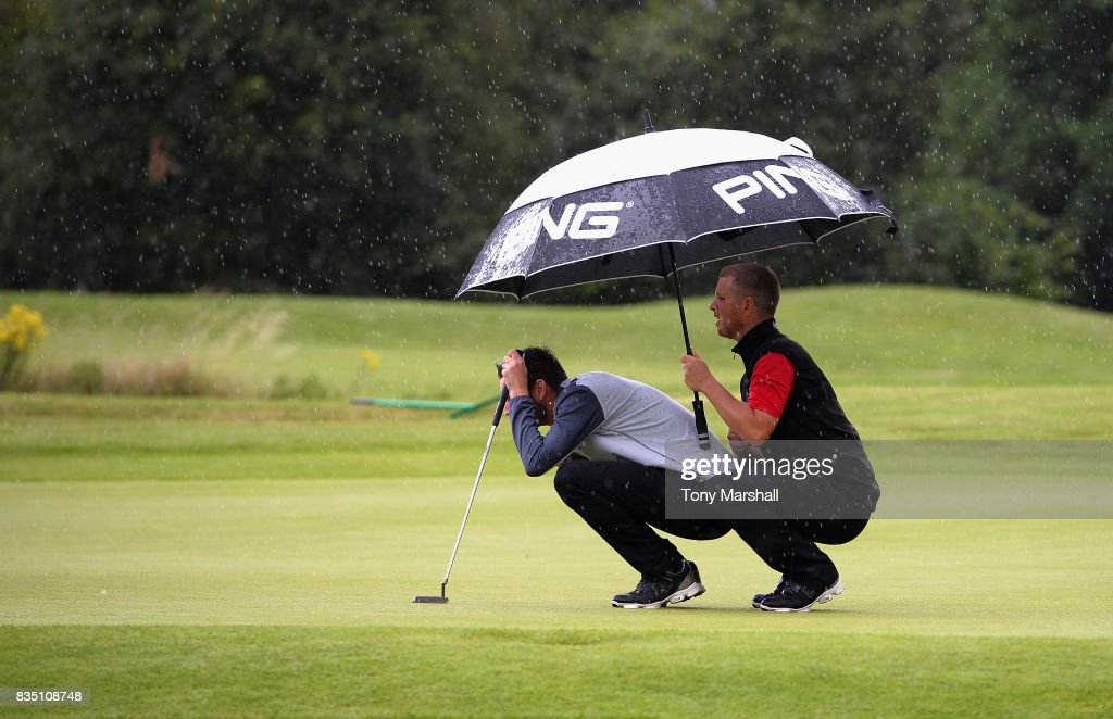 Barry Forster of North Wilts Golf Club and Dan Carter of Upavon Golf Club line up a putt under an umbrella in the rain during the Golfbreaks.com PGA Fourball Championship - Day 3 at Whittlebury Park Golf & Country Club on August 18, 2017 in Towcester, England.
