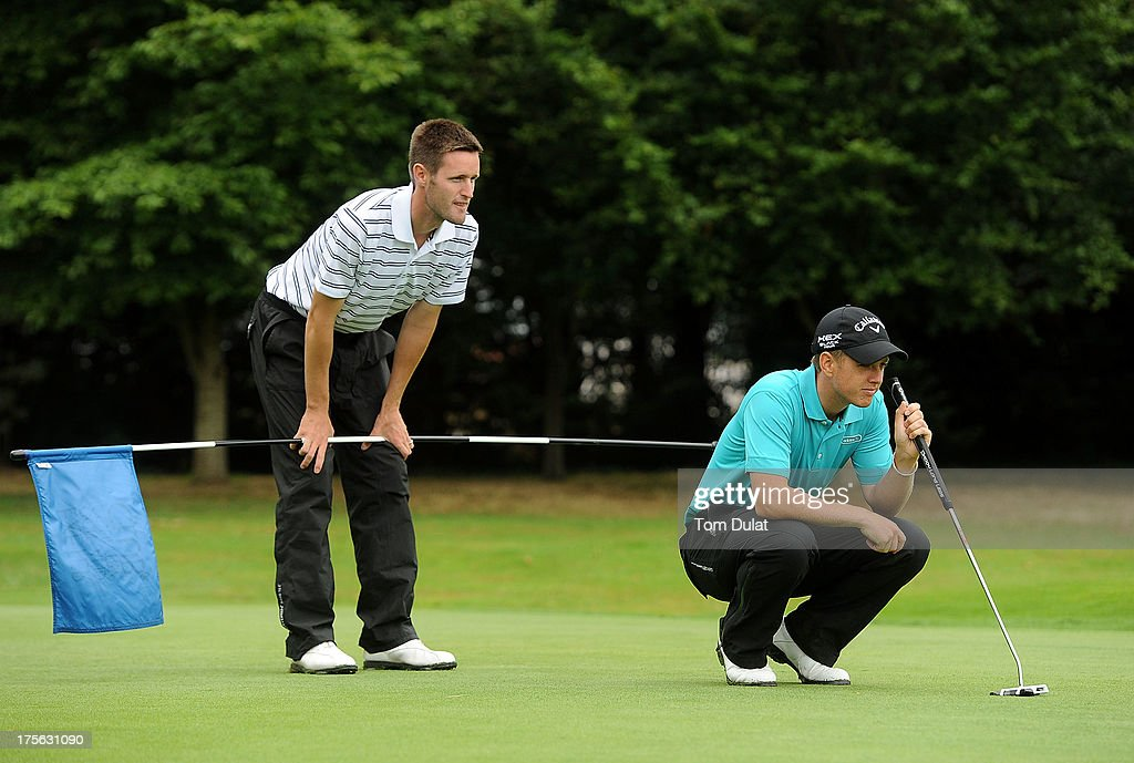 Barry Forster of North Wilts Golf Club (L) and Daniel Carter of Upavon Golf Club (R) line up a putt on the 18th green during the Golfbreaks.com PGA Fourball Regional Qualifier at Exeter Golf and Country Club on August 5, 2013 in Exeter, England.