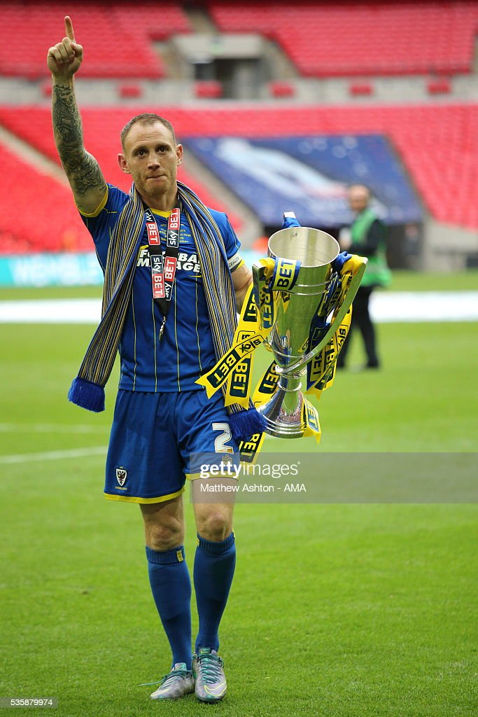Barry Fuller of AFC Wimbledon celebrates promotion after victory in the Sky Bet League Two Play Off Final between Plymouth Argyle and AFC Wimbledon at Wembley Stadium on May 30, 2016 in London, England.