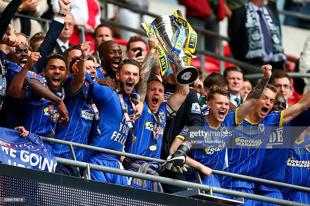 Barry Fuller of Wimbledon lifts the trophy with his teammates after they win the Sky Bet League Two Play Off Final match between Plymouth Argyle and AFC Wimbledon at Wembley Stadium on May 30, 2016 in London, England.