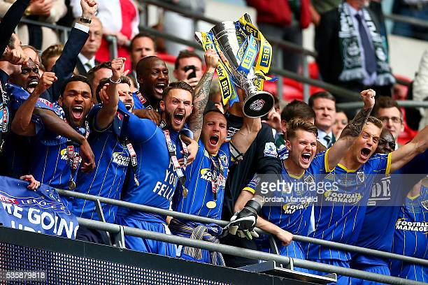 Barry Fuller of Wimbledon lifts the trophy with his teammates after they win the Sky Bet League Two Play Off Final match between Plymouth Argyle and...