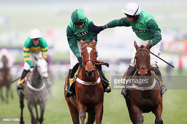 Barry Geraghty riding Peace and Co is congratulated by Daryl Jacob riding Top Notch after victory in the JCB Triumph Hurdle race during day four of...