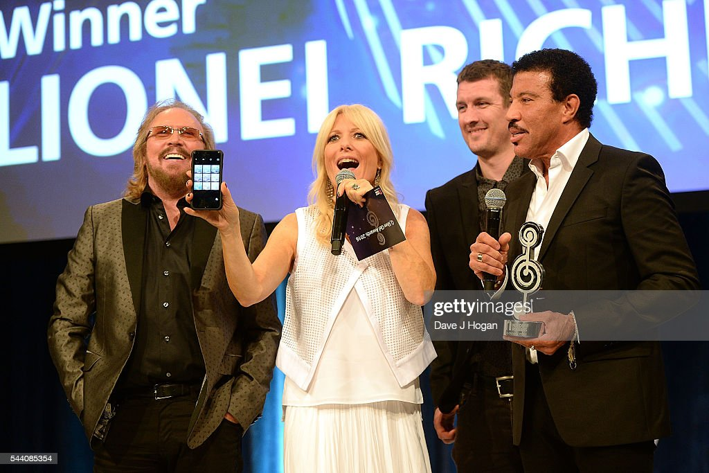Barry Gibb, Gaby Roslin, guest and Lionel Richie take a selfie on stage during the Nordoff Robbins O2 Silver Clef Awards on July 1, 2016 in London, United Kingdom.