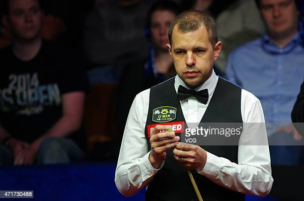 Barry Hawkins of England chalks his cue against Shaun Murphy of England during the semifinal match on day thirteen of the 2015 Betfred World Snooker...