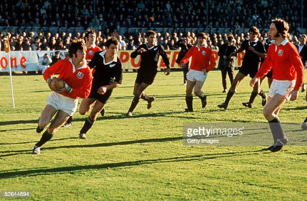 Barry John of the British Lions is pursued by Tane Norton of New Zealand during the First Test match between New Zealand and the British Lions at...