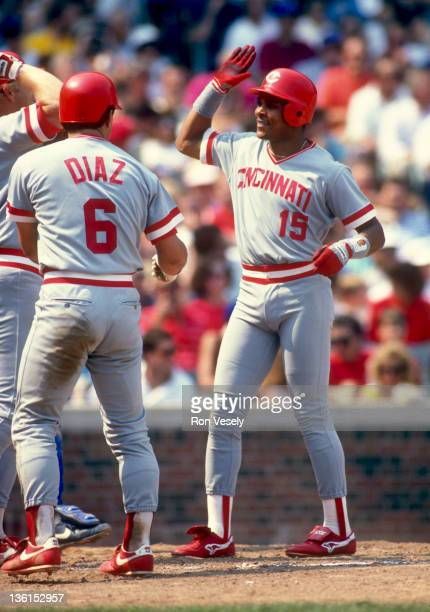 Barry Larkin celebrates with Bo Diaz of the Cincinnati Reds after Larkin hit a home run during an MLB game against the Chicago Cubs at Wrigley Field...