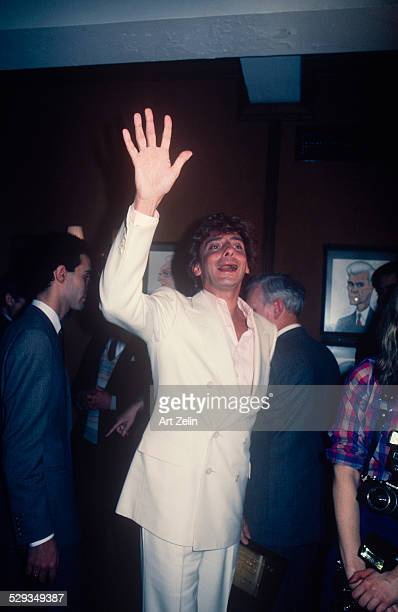 Barry Manilow waving to a friend wearing a white suit and pink shirt at Sardi's circa 1980 New York