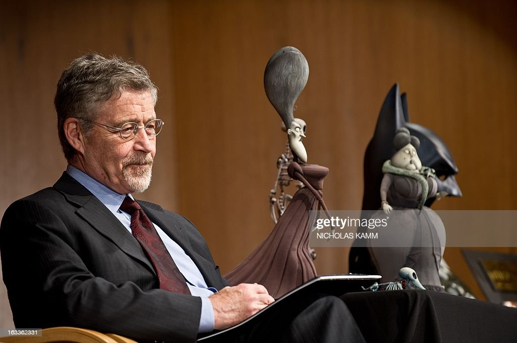Barry Meyer, chairman of Warner Bros., sits next to figures from Tim Burton's Corpse Bride during a ceremony at the National Museum of American History as Warner Bros. donates memorabilia to the museum on March 8, 2013. More than 30 objects from 13 Warner Bros. films spanning 1942 to 2005 will be added to the National Museum of American History's entertainment collections, including Halle Berry's costume from the 2004 film Catwoman, props from the 2005 film Charlie and the Chocolate Factory and a selection of stop-action puppets used by director Tim Burton for the 2005 film Corpse Bride. AFP PHOTO/Nicholas KAMM