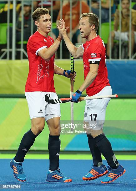 Barry Middleton of Great Britain high fives Harry Martin after Middleton scored a goal against Brazil during the hockey game on Day 4 of the Rio 2016...