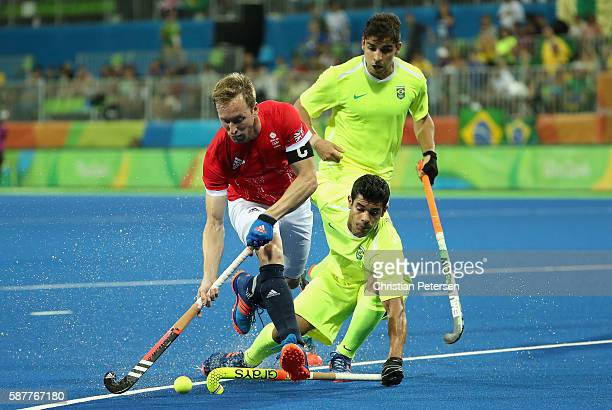 Barry Middleton of Great Britain moves the ball past Joaquin Lopez and Harry Martin of Brazil during the hockey game on Day 4 of the Rio 2016 Olympic...