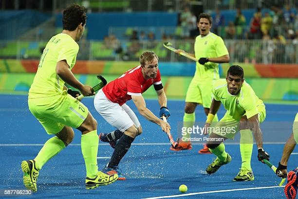 Barry Middleton of Great Britain moves the ball past Paulo Batista of Brazil during the hockey game on Day 4 of the Rio 2016 Olympic Games at the...