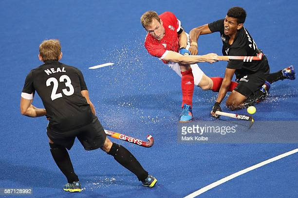 Barry Middleton of Great Britain passes under pressure from Arun Panchia of New Zealand during the men's pool A match between Great Britain and New...