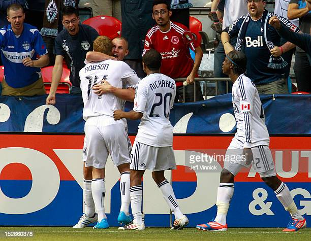 Barry Robson of the Vancouver Whitecaps FC hugs goal scorer Kenny Miller while Dane Richards and Darren Mattocks approach against the Colorado Rapids...