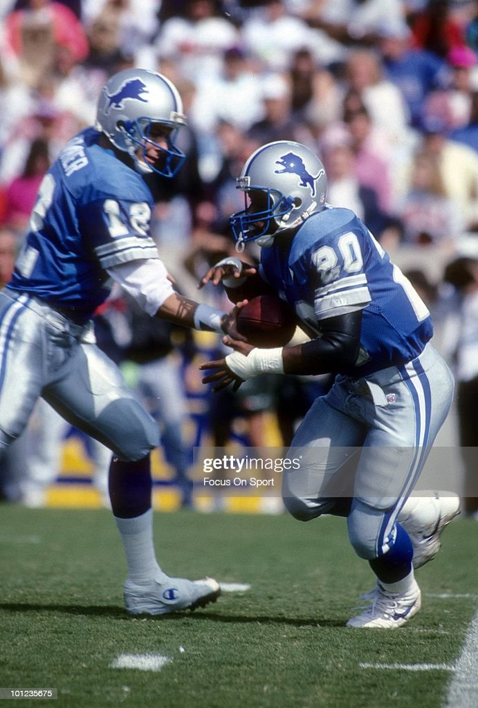 Barry Sanders #20 of the Detroit Lions looks to take the hand off from quarterback Erik Kramer #12 against the Tampa Bay Buccaneers November 10, 1991 during an NFL football game at Tampa Stadium in Tampa Bay, Florida. The Buccaneers won 30 - 21. Sanders played for the Lions from 1989-98.