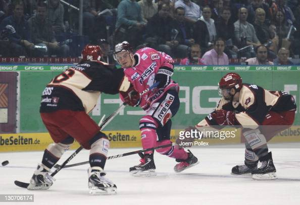 Barry Tallackson of Berlin and Andre Reiss and Scott King of Hannover battle for the puck during the DEL Bundesliga match between EHC Eisbaeren...