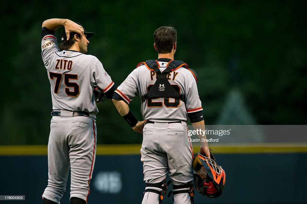 Barry Zito #75 and Buster Posey #28 of the San Francisco Giants look on as Hunter Pence #8 (not pictured) is looked after by trainers after he slammed into the outfield wall during a game at Coors Field on August 26, 2013 in Denver, Colorado.