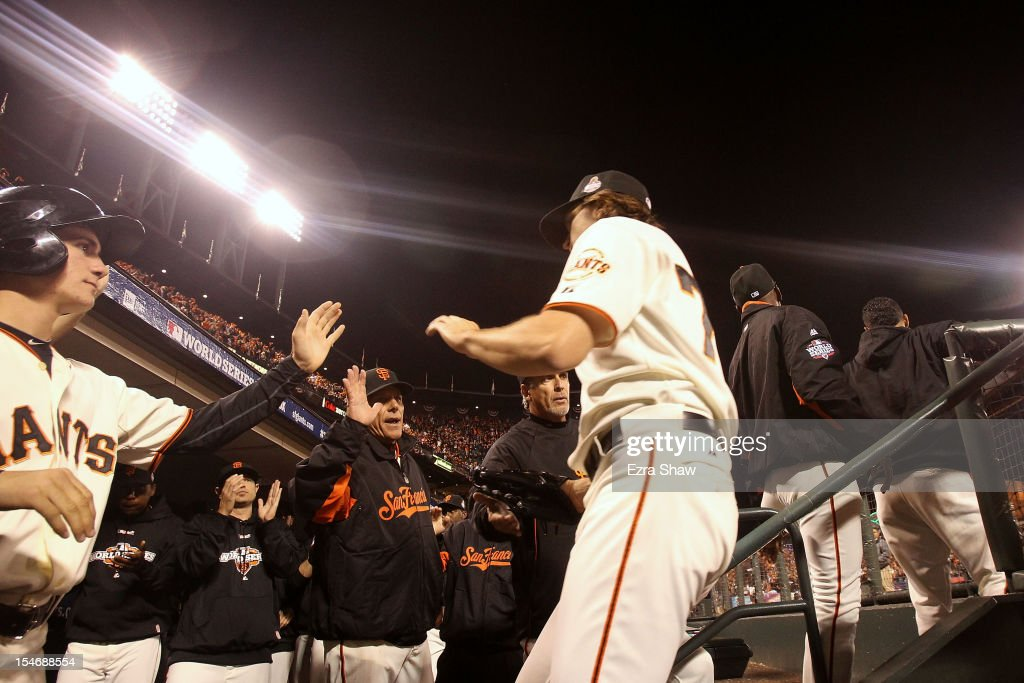 Barry Zito of the San Francisco Giants high fives his teammates in the dugout after being relieved by Tim Lincecum in the sixth inning against the...