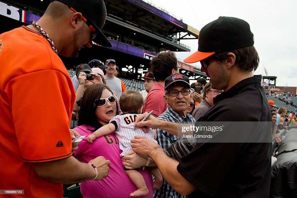 Barry Zito #75 of the San Francisco Giants signs a baby before a game against the Colorado Rockies at Coors Field on May 17, 2013 in Denver, Colorado.