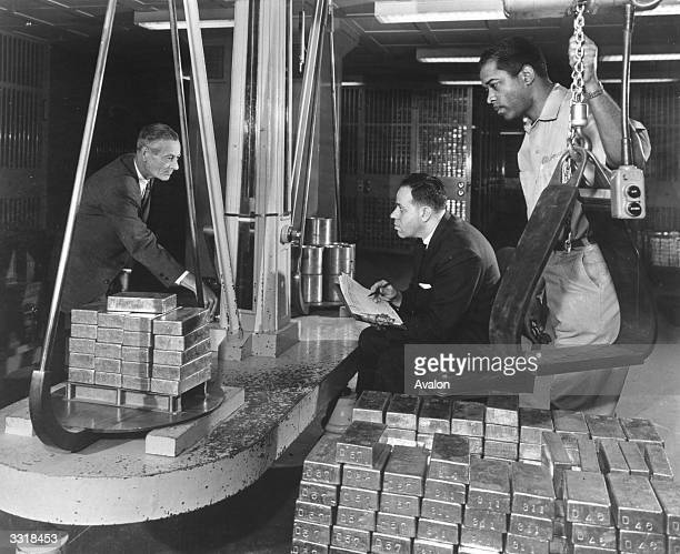 Bars of gold being weighed and earmarked for international exchange transactions in the top security vaults of New York's Federal Reserve Bank