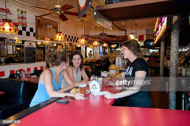 Bartender Alli Connolly at Charlie's Kitchen in Harvard Sq Cambridge MA on August 21 2013 with customers Alix Easton of Brighton and Nina Krane of...