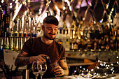 Hipster bartender is pouring drinks behind the bar.