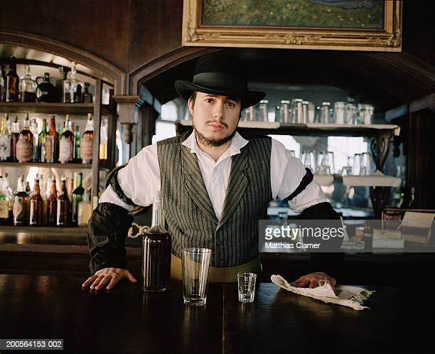 Bartender behind bar counter in saloon, portrait