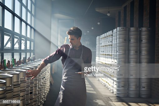 Bartender counting beer keg's and using tablet