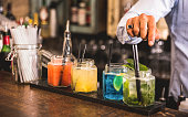 Bartender hand at multicolored fashion drink with straw on vintage glass cups in fashion cocktail bar - Food and beverage concept with professional barman working at mixology restaurant - Vivid colors