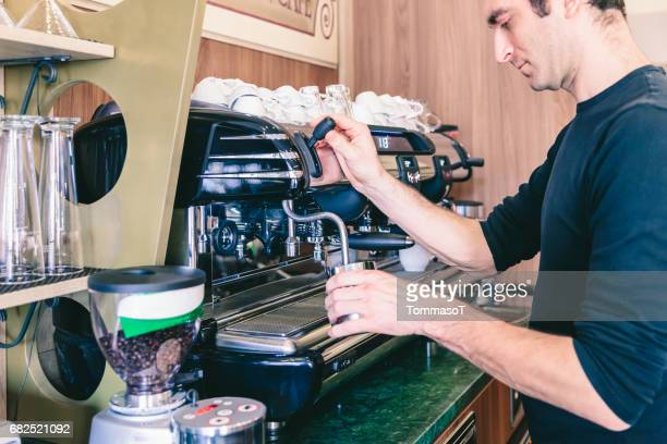 Bartender heating milk for cappuccino