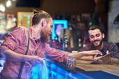 Side view portrait of modern bearded bartender talking to client at bar counter in pub, helping him choose drinks via digital tablet