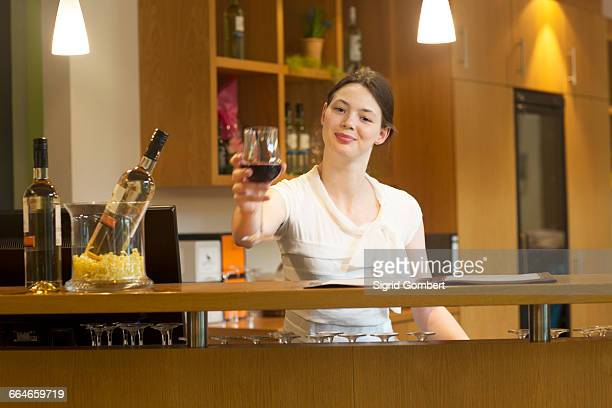 Bartender in wine bar holding wine glass looking at camera smiling