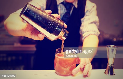 Bartender is making a cocktail, toned : Stock Photo
