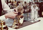 Bartender is pouring liquor in golden shaker, toned image