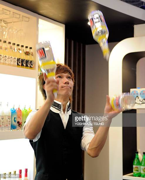 A bartender juggles bottles of makkolli Korean liquor for a cocktail at the annual 'Foodex' food exhibition in Chiba suburban Tokyo on March 1 2011...