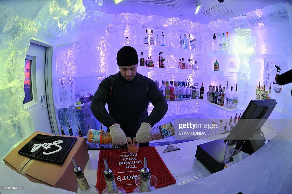 Bartender Julio Roman mixes a drink in the Minus 5 Ice Bar during a preview at the New York Hilton Midtown Hotel July 9, 2013 in New York. The bar is constructed of 90 tons of ice and is kept at a temperature of -5 degrees C (23 degrees F). Guests are given parkas, gloves and hats and for an additional fee, fur coats. Designs in the wall and around the bar are carved by ice sculptor Peter Slavin. AFP PHOTO/Stan HONDA