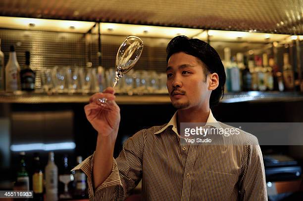 Bartender looking at a glass