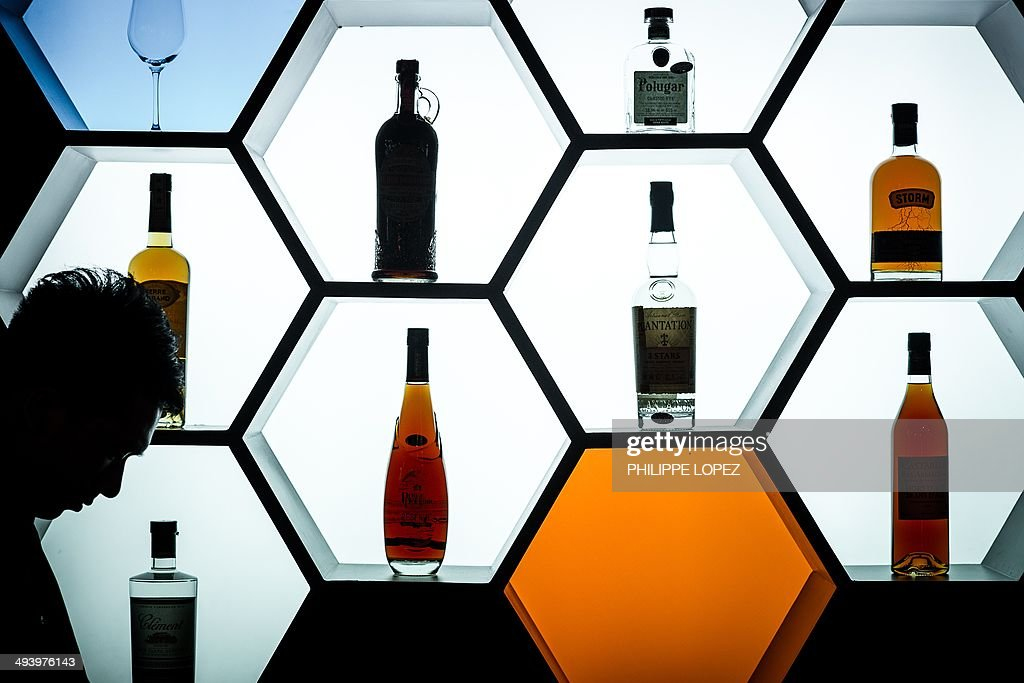 A bartender (L) looks down in front of bottles displayed at Vinexpo Asia Pacific in Hong Kong on May 27, 2014. Asia's biggest wine and spirits fair opened in Hong Kong, drawing the world's top producers from France to Chile despite China reporting the first decline in wine consumption for a decade. AFP PHOTO / Philippe Lopez