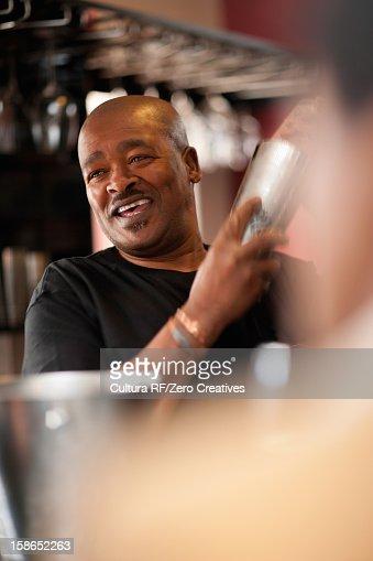 Bartender mixing drinks at bar : Stock Photo