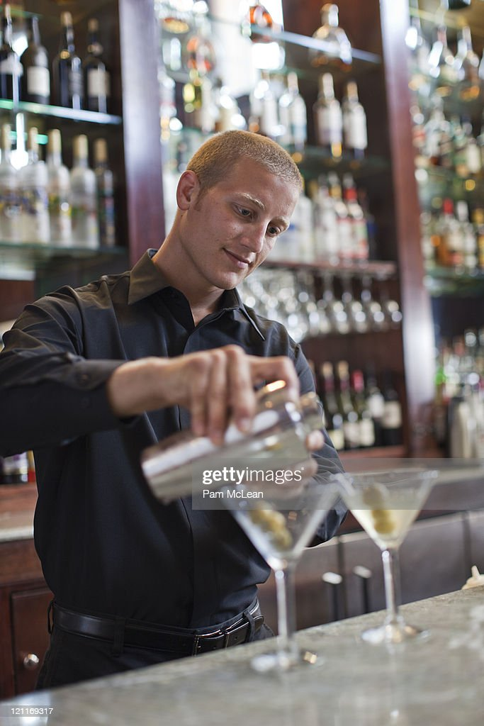 Bartender mixing martinis : Stock Photo